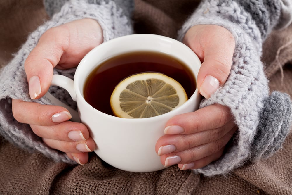 Woman's hand holding cup of antioxident tea with lemon on a cold day