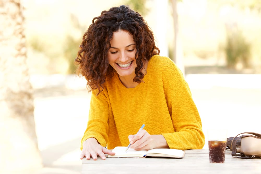 young woman sitting at table writing in diary